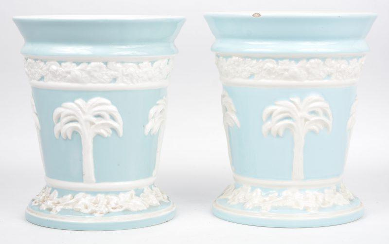 Een paar porseleinen bloempotjes met wit reliëfdecor van palmbomen op blauwe fond. Onderaan gemerkt. Eén met randschilfer.