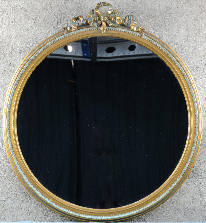 Een spiegel in verguld houten lijst in Lodewijk XVI-stijlmet een strik  bovenaan.