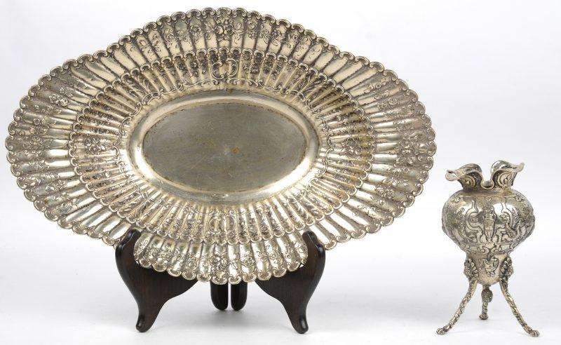 Een ovale schotel van gedreven zilver. Duitse keuren, 800/1000, evanals een zilveren vaasje met drie pootjes. h: 14 cm.