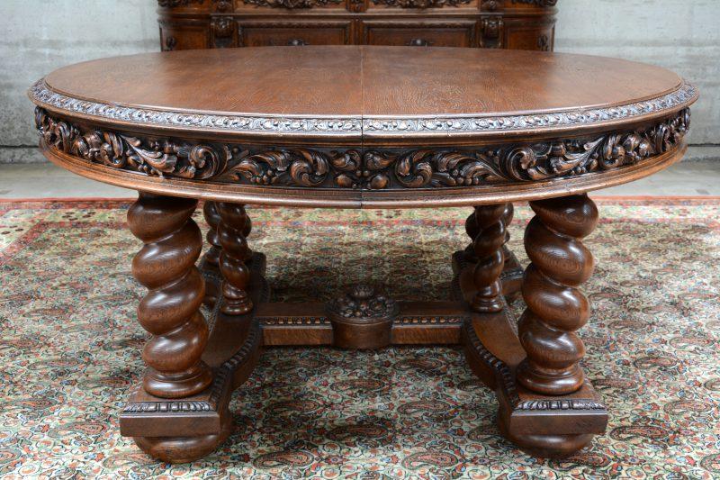 Een verlengbare ronde eikenhouten tafel met getorste poten en de gordel versierd met gebeeldhouwde bladermotieven.