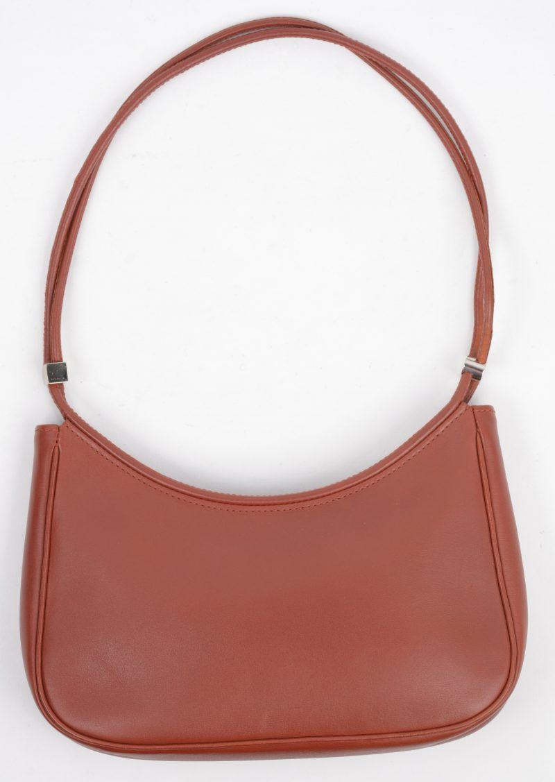 Een rood lederen handtas in draagtas.
