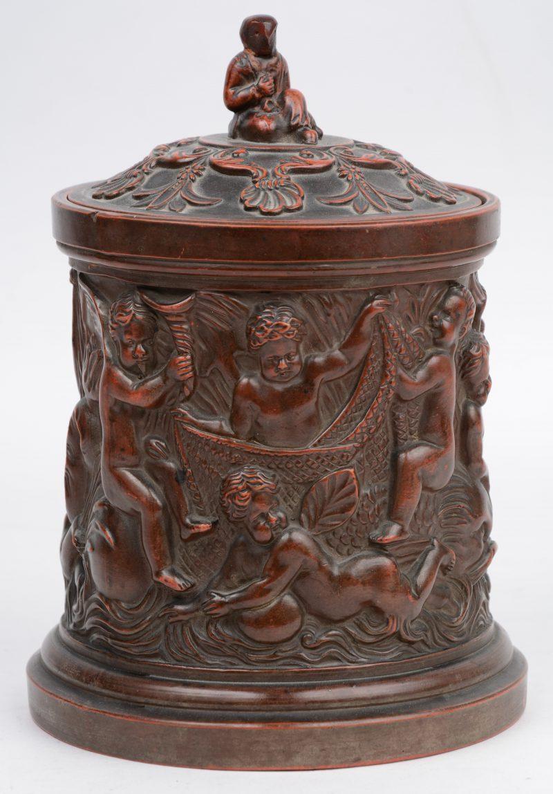 Een tabakspot van terracotta, versierd met een reliëfdecor van putti. Onderaan gemerkt 'F.G.'.